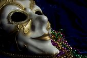 picture of mardi gras mask  - White and gold Mardi Gras mask and beads on a blue velvet background - JPG