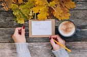 Womans Hands Holding A Pen Writing Hello Autunm Text On Paper With Craft Envelope. Cup Of Coffee, Ca poster