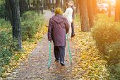 Senior Woman Enjoying Nordic Walking At Beautiful Colorful Autumn Park. Old Age Person Doing Pole Wa poster