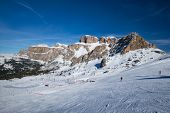 View of a ski resort piste with people skiing in Dolomites in Italy. Ski area Belvedere. Canazei, It poster