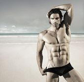 foto of buff  - Sexy portrait of a hot buff male fitness model pulling at his bikini briefs on the beach - JPG