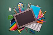 Blank blackboard, computer keyboard, stationery accessories: pencils, pens, other office supplies on poster