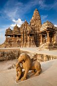stock photo of kandariya mahadeva temple  - King and lion fight statue and Kandariya Mahadev temple - JPG