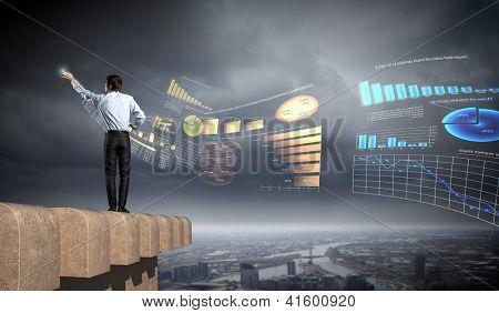 hombre joven empresario permanente con dibujo nuevo diagrama contra el fondo de la ciudad