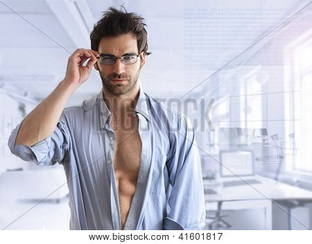 Sexy hunk male model with open shirt in modern business setting with blue toning