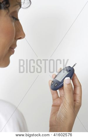 African American woman checking diabetes test