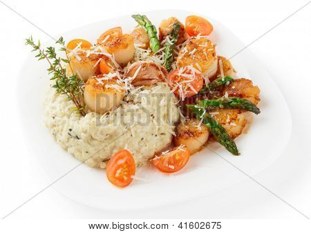 Risotto with pan seared sea scallops, cheese and vegetables  isolated on white background