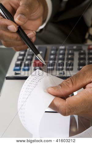 Hands of male accountant with calculator paper tape