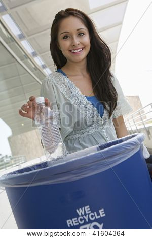 Young woman throwing plastic bottle in dustbin