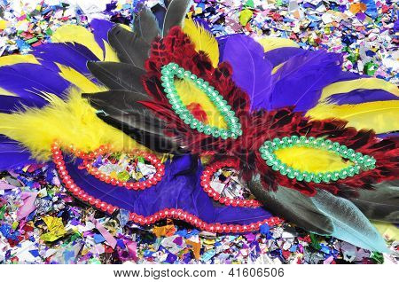 some carnival masks with feathers of different colors on a pile of confetti