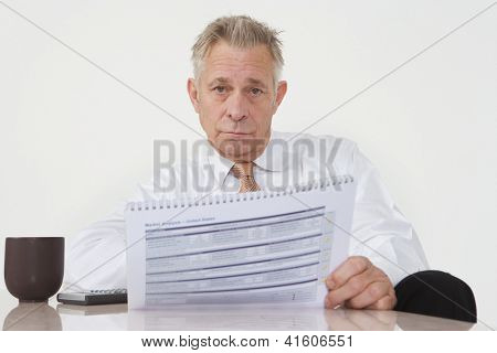 Senior businessman sitting with investment brochure at office