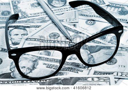 black eyeglasses and pen on a pile of dollar bills