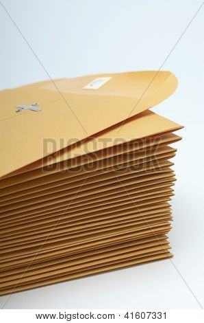 Stack of brown confidential paper folders over white background