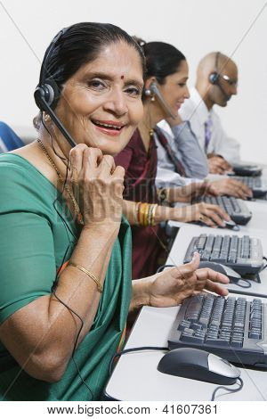 Portrait of a happy senior female customer service operator working with colleagues at office