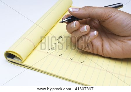 Closeup of woman with pen scheduling task list on notepad over white background