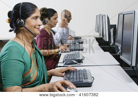 Happy senior female customer service operator working with colleagues at office
