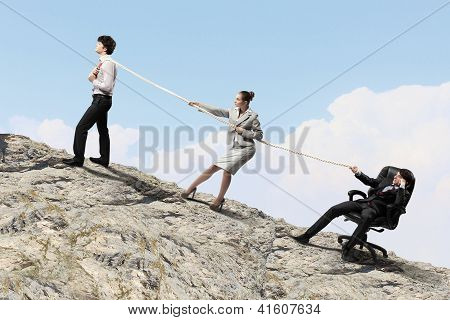 Three business people pulling rope