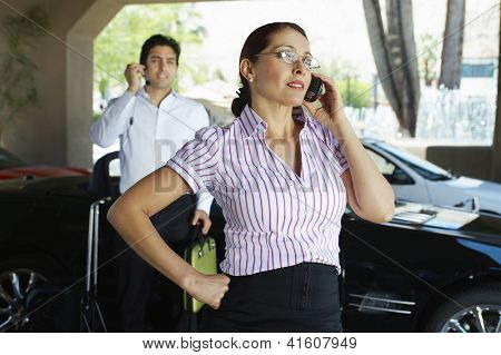 Business woman communicating on cell phone with coworker and car in the background