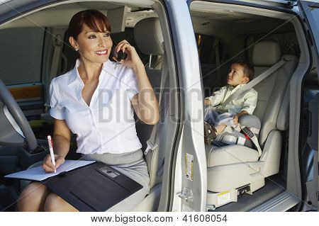 Happy business woman writing notes while communicating on cell phone with son sitting on backseat