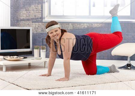 Happy young fat Woman Ausübung zu Hause Stock, lächelnd.