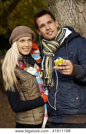 Attractive young couple listening to music, using mp3 player in park at autumn, smiling.