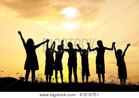 Group of happy children standing on meadow at summer sunset