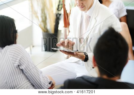 Portrait of modern couple talking to manager while discussing conditions of mortgage using tablet