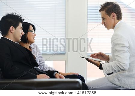 Portrait of a happy young couple talking to financial advisor at home