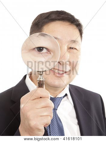 Asian businessman in a suit looking through a magnifying glass. Isolated on white background