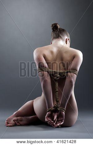 Naked woman posing with shibari in studio