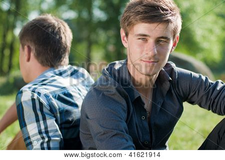 Two Young Man Sitting Together Outdoors