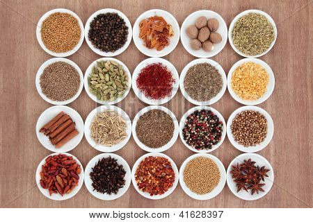Large spice and herb selection in white porcelain bowls over papyrus background.