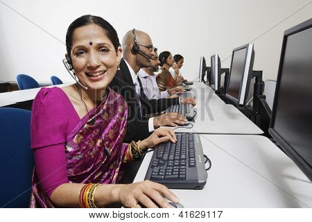 Portrait of a female customer service operator in saree with colleagues in  the office