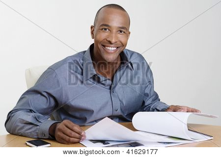 Portrait of an African American businessman going through building models in office