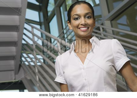 Low angle view of a beautiful Indian woman smiling in office