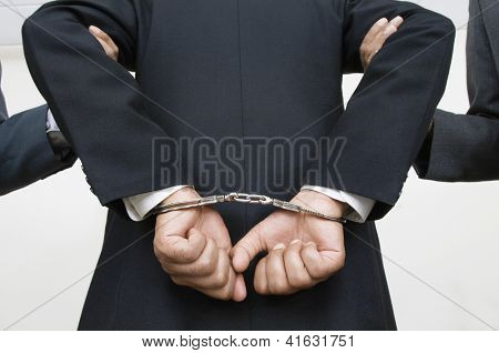 Rear view of businessman with handcuffs while partners holding his arms isolated over white background