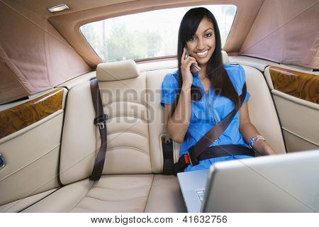 Portrait of an Indian business woman using laptop while communicating on cell phone in car