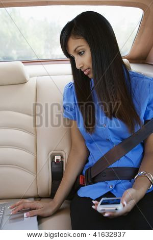 Young Indian business woman using laptop in car