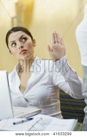 Young business woman showing stop gesture to her colleague in office