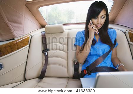 An Indian business woman using laptop while communicating on mobile phone in car