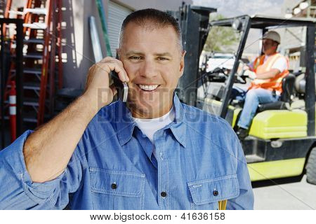 Portrait of a happy male industrial worker communicating on cell phone with his coworker in the background