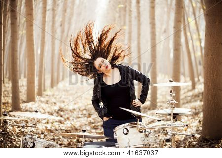 Young drummer playing with her hair