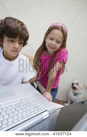 Preadolescent children using laptop with dog sitting besides
