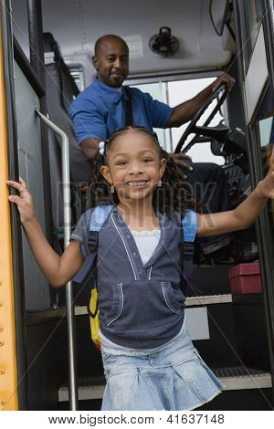Portrait of a cute little girl getting down from the bus while driver looking at her