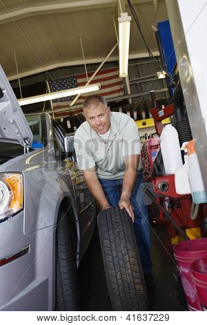 Portrait of a male mechanic changing spare car tire at workshop