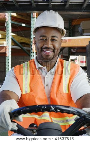 Portrait of a happy African American male industrial worker driving forklift at workplace