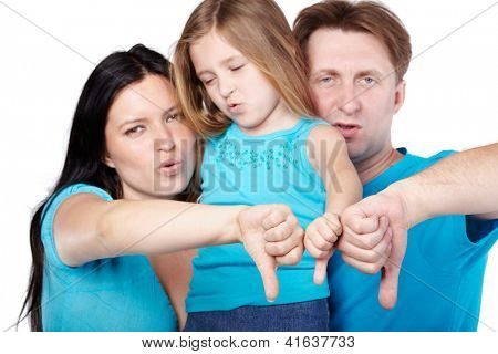 Family of three in blue shirts with disagreeable faces gives their thumbs down, focus on thumbs.