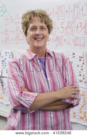 Portrait of a confident mature female teacher standing with arms crossed against whiteboard