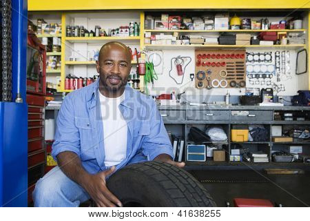 Portrait of a happy African American male mechanic working at workplace