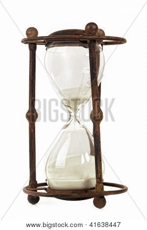 Antique hourglass in rusty metal frame, isolated on white.